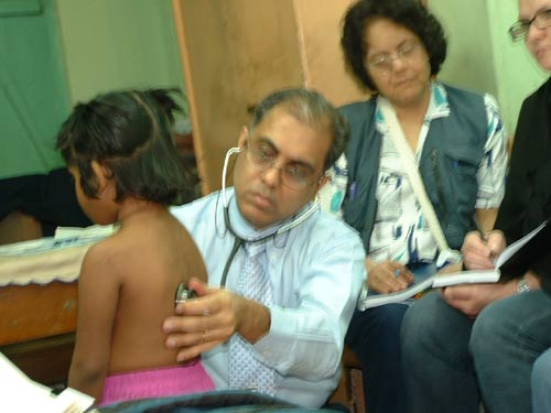 Dr. Banerjea examining Tuberculosis of a child; overseas homoeopaths are observing the case.